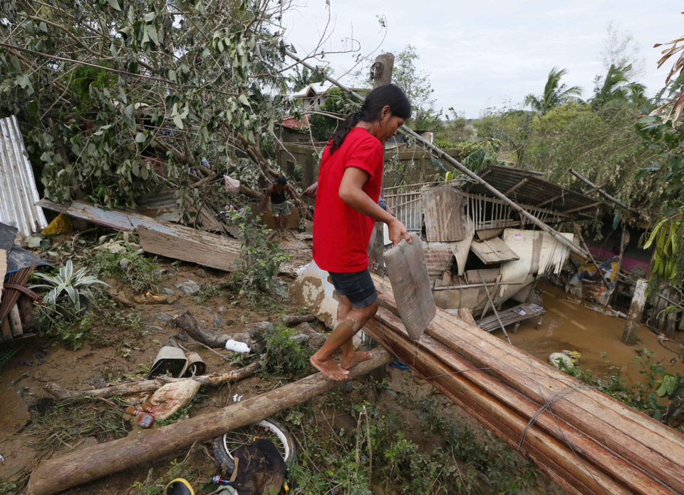 Photo - Residents begin cleaning up their homes in Cabanatuan, northern Philippines, Tuesday, Oct. 20, 2015, two days after Typhoon Koppu battered Cabanatuan city and nearby provinces. Slow-moving Typhoon Koppu blew ashore with fierce wind in the northeastern Philippines early Sunday, toppling trees and knocking out power and communications and forcing the evacuation of thousands of villagers (AP Photo/Bullit Marquez)