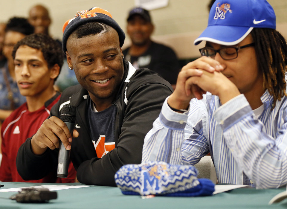 Photo - Khari Harding, middle, looks at Phillip Sumpter while speaking during the signing day ceremony at Edmond Santa Fe High School in Edmond, Okla., Wednesday, Feb. 6, 2013. Harding will play football at Auburn. Sumpter has signed to play football at Memphis. At left is Matthew Giudice who will play soccer and run track at Hastings College. Photo by Nate Billings, The Oklahoman
