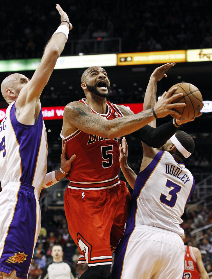 Chicago Bulls' Carlos Boozer (5) tries to get a shot off as Phoenix Suns' Marcin Gortat, left, of Poland, and Jared Dudley (3) defend during the first half of an NBA basketball game, Wednesday, Nov. 14, 2012, in Phoenix. (AP Photo/Ross D. Franklin)