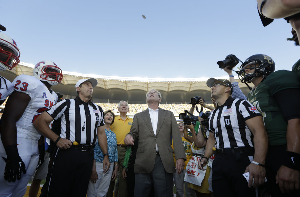 Photo - Former President George W. Bush tosses the coin before the NCAA college football game between SMU and Baylor Sunday, Aug. 31, 2014, in Waco, Texas. (AP Photo/LM Otero)