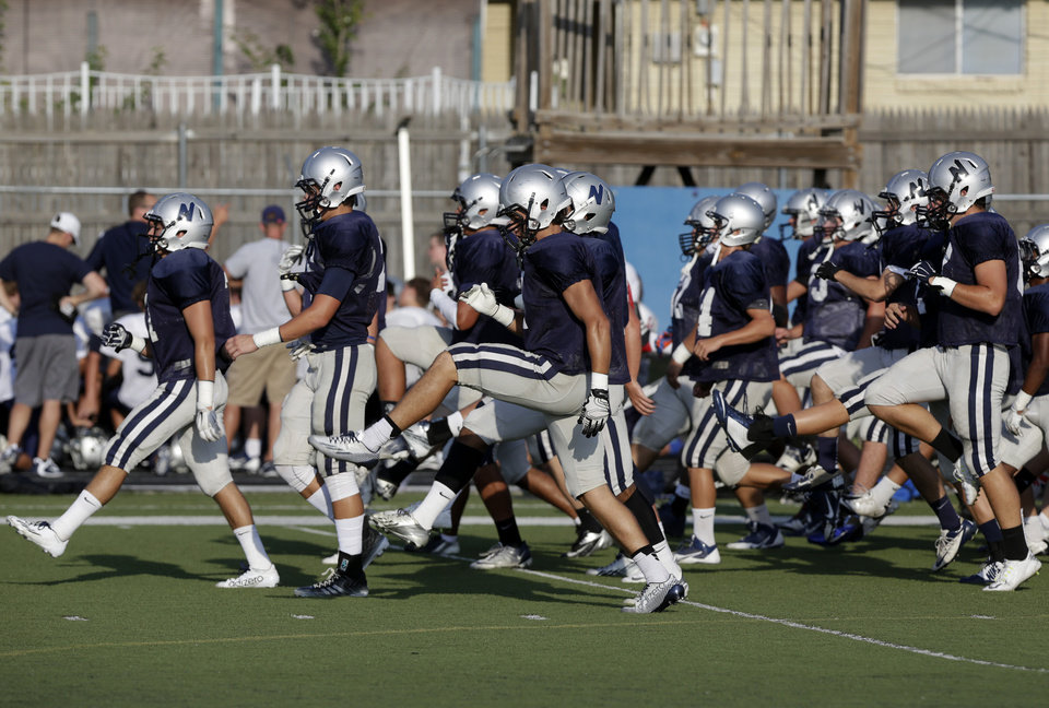 Photo - Edmond North warms up before a scrimmage at Putnam City West High School in Bethany, Thursday, Aug. 21, 2014.  Photo by Garett Fisbeck, For The Oklahoman