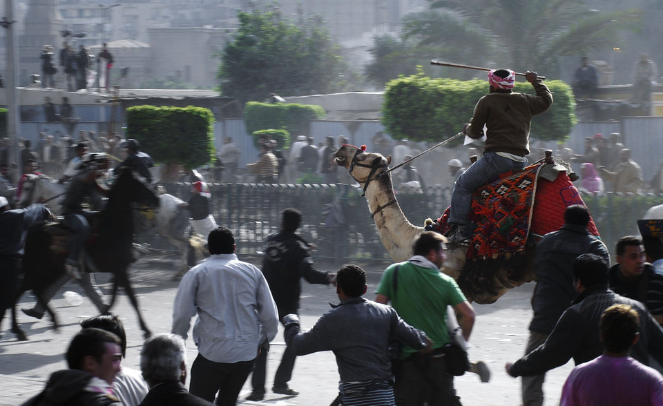 Photo - FILE - In this Wednesday, Feb. 2, 2011 file photo, supporters of President Hosni Mubarak, riding camels and horses, fight with anti-Mubarak protesters in Cairo, Egypt. As Egyptians mark the third anniversary of their revolution against autocrat Hosni Mubarak in the name of democracy, there has been a powerful sign of the country's stunning reversals since: letters of despair by some of the prominent activists who helped lead the uprising, leaked from the prisons where they are now jailed. The letters show a daunted and broken spirit, no longer speaking of imminent democracy, but of injustices and a failed struggle.(AP Photo/Mohammed Abu Zaid, File)