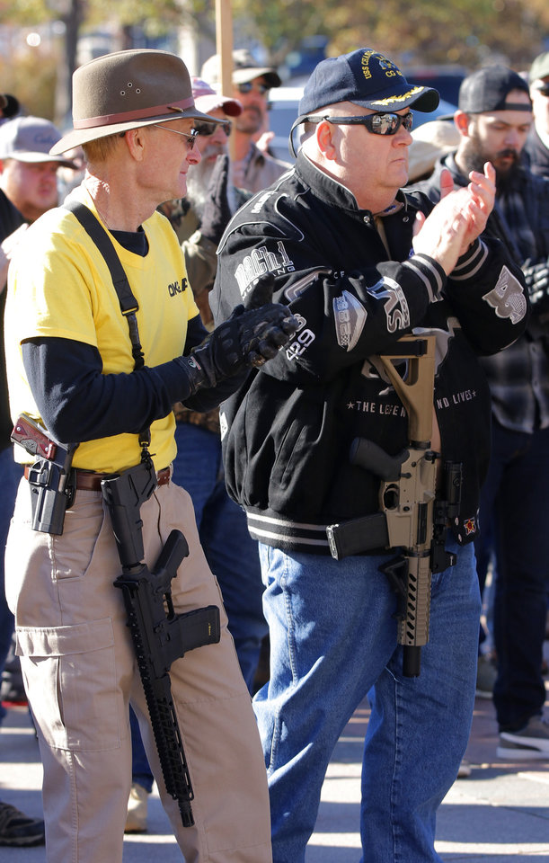 Photo - Joe Kelley, Broken Arrow, and Scott Winters, Moore, listen to speakers. Second Amendment supporters rally at the state Capitol to celebrate the permitless carry law taking effect. Friday, November 1, 2019. [Doug Hoke/The Oklahoman]