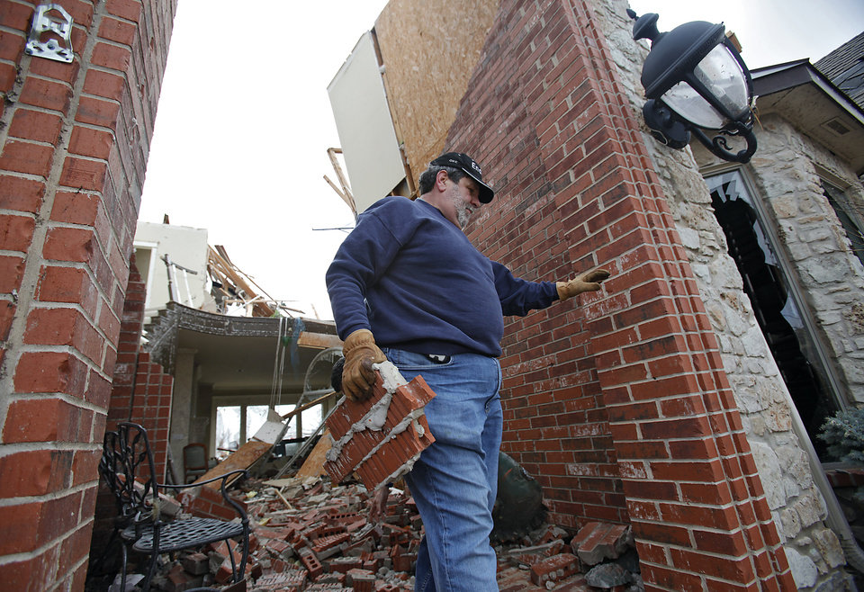 Ray Cales clears debris from his home that was damaged in the Oak Tree addition on Wednesday, Feb. 11, 2009, after a tornado hit the area on Tuesday in Edmond, Okla.  PHOTO BY CHRIS LANDSBERGER, THE OKLAHOMAN