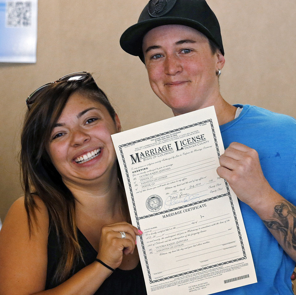 Photo - Samantha Getman, right, and Victoria Quintana show their marriage license at the Denver Clerk's office on Thursday, July 10, 2014. They were the first couple to receive a marriage licence in Denver, after clerk Debra Johnson began issuing licenses to same sex couples on Thursday. (AP Photo/Ed Andrieski)
