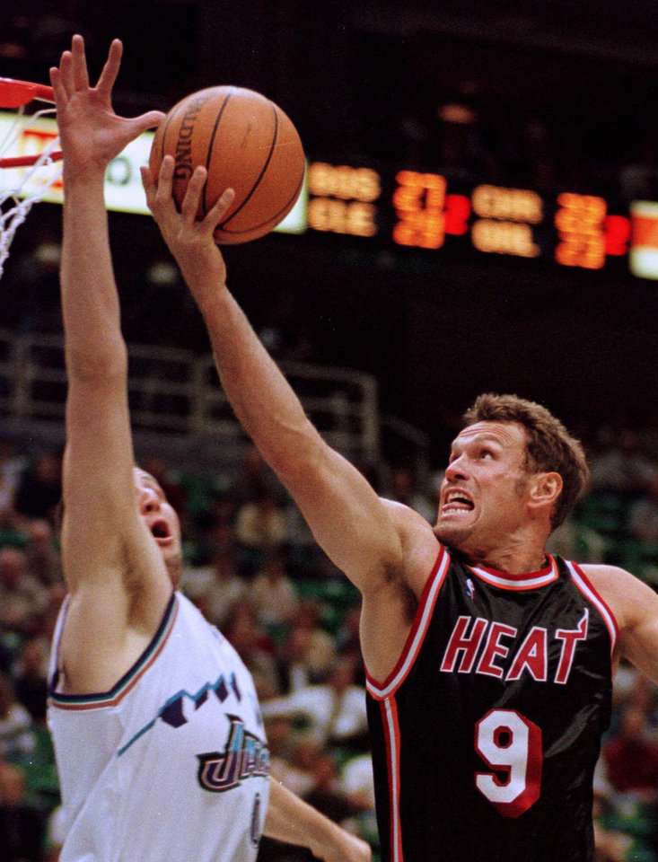 Photo - Utah Jazz basketball center Greg Ostertag blocks the shot of Miami Heat guard Dan Majerle (9) in the first quarter Tuesday, March 23, 1999, in Salt Lake City.  (AP Photo/Douglas C. Pizac)