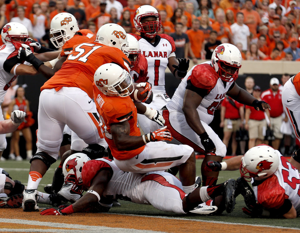 Photo - Oklahoma State's Jeremy Smith (31) scores a touch down in the first quarter during a college football game between the Oklahoma State University Cowboys (OSU) and the Lamar University Cardinals at Boone Pickens Stadium in Stillwater, Okla., Saturday, Sept. 14, 2013. Photo by Sarah Phipps, The Oklahoman