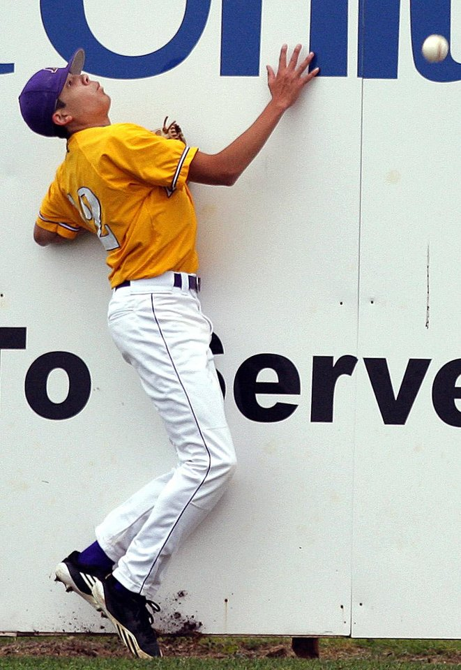 Photo - Anadarko's Kolby Williams hits the wall as he chases down a fly ball during the 4A high school baseball playoff game between Hilldale and Anadarko at Shawnee High School in Shawnee, Okla., Friday, May 11, 2012. Photo by Sarah Phipps, The Oklahoman