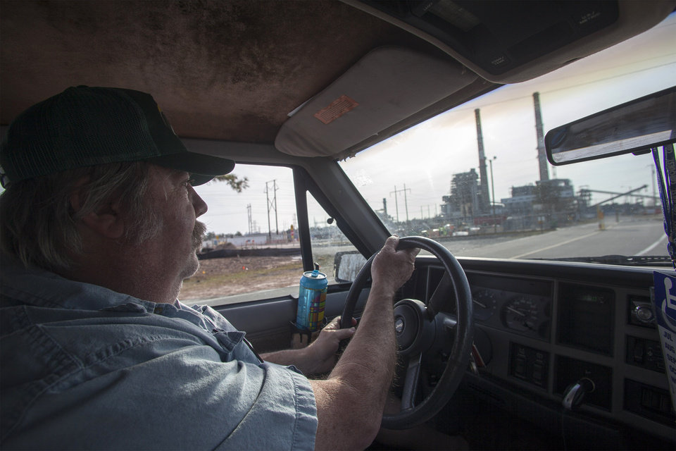 Photo - Flemington Road community resident Kenneth Sandlin of Wilmington, N.C., drives by the L.V. Sutton Complex operated by Duke Energy on Wednesday, Feb. 19, 2014. Sandlin is part of the small community that feels nearby Sutton Lake and well water could be polluted from spill off and seepage from large coal ash ponds at the facility. In the wake of Duke Energy's massive coal ash spill in Eden, people in the Flemington community are paying close attention to the environmental disaster unfolding 200 miles to the northwest along the Dan River.   (AP Photo/Randall Hill)