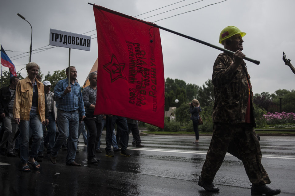Photo - Miners, one of them carrying a sign with the name of the mine Trudovskaya, march in support of peace in downtown Donetsk, eastern Ukraine, Wednesday, June 18, 2014.  Hundreds of miners went on a protest walk through the streets of central Donetsk on Wednesday, trying to express support for a peaceful resolution to the eastern Ukraine conflict, ongoing for almost four months. (AP Photo/Evgeniy Maloletka)
