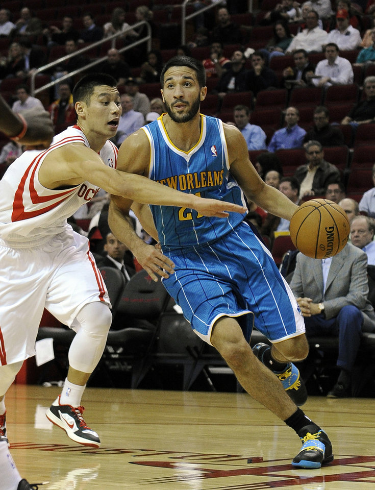 Photo -   Houston Rockets' Jeremy Lin, left, reaches for New Orleans Hornets' Greivis Vasquez (21) in the first half of an NBA basketball game, Wednesday, Nov. 14, 2012, in Houston. (AP Photo/Pat Sullivan)