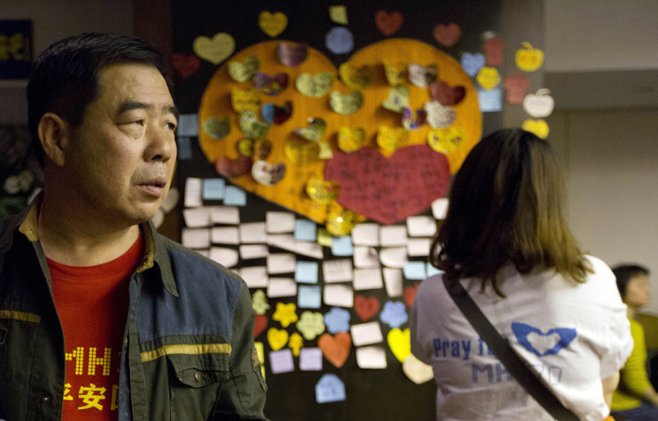 Photo - Relatives of Chinese passengers onboard the Malaysia Airlines MH370 stand near messages of well wishes, pasted onto the wall,  in a prayer room in Beijing, China, Thursday, April 3, 2014.  No trace of the Boeing 777 has been found nearly a month after it vanished in the early hours of March 8 on a flight from Kuala Lumpur to Beijing with 239 people on board. (AP Photo/Ng Han Guan)