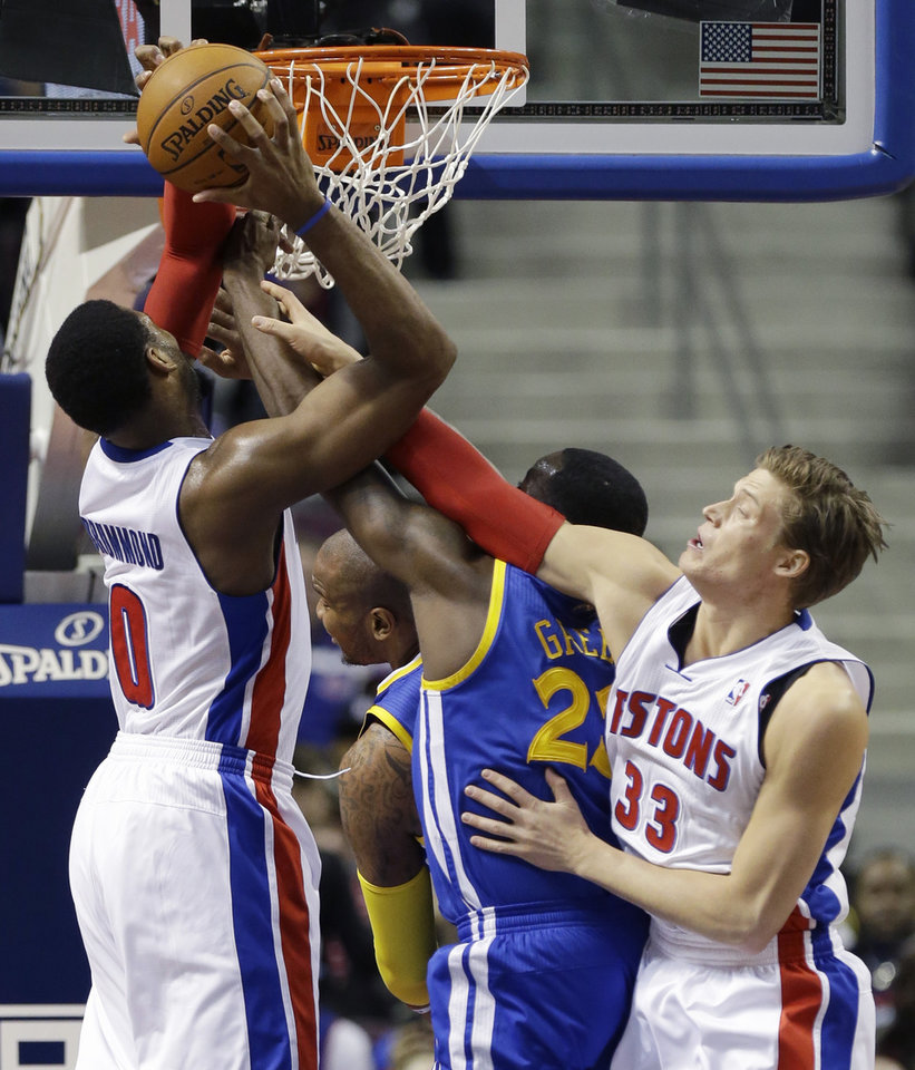 Detroit Pistons center Andre Drummond (0) recovers a rebound as teammate forward Jonas Jerebko (33) of Sweden and Golden State Warriors forward Draymond Green (23) reach in during the first half of an NBA basketball game in Auburn Hills, Mich., Monday, Feb. 24, 2014. (AP Photo/Carlos Osorio)