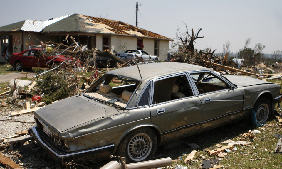 Photo - A car, house and other debris sit damaged in Granbury, Texas, on Friday May 17, 2013. On Wednesday, powerful storms produced 16 tornadoes in the area that left six dead. (AP Photo/Mike Fuentes)