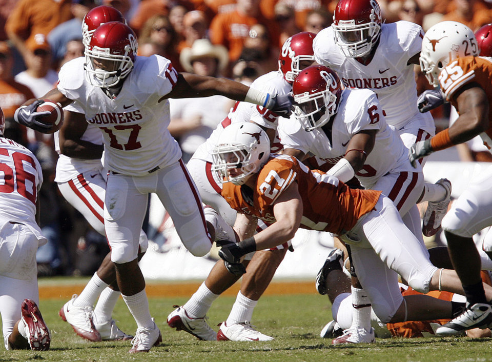 Photo - Oklahoma's Mossis Madu (17) tries to get away from Texas' Nolan Brewster (27) during the Red River Rivalry college football game between the University of Oklahoma Sooners (OU) and the University of Texas Longhorns (UT) at the Cotton Bowl in Dallas, Texas, Saturday, Oct. 17, 2009. Photo by Chris Landsberger, The Oklahoman