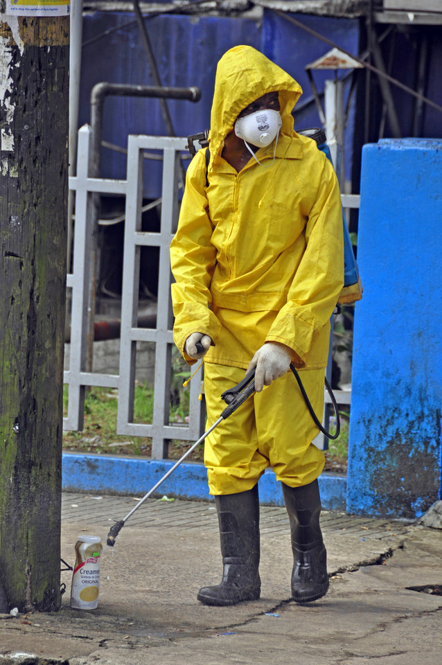 Photo - An employee  of the Monrovia City Corporation sprays disinfectant on a street, in front of a building in a bid to prevent the spread of  the deadly Ebola virus, in the city of Monrovia, Liberia, Friday, Aug. 1, 2014 .U.S. health officials warned Americans not to travel to the three West African countries hit by the worst recorded Ebola outbreak in history. The travel advisory issued Thursday applies to nonessential travel to Guinea, Liberia and Sierra Leone, where the deadly disease has killed more than 700 people this year. (AP Photo/Abbas Dulleh)