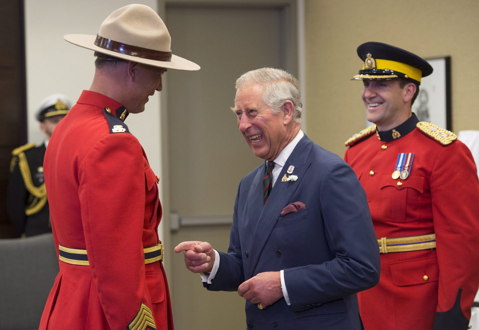 Photo - Prince Charles, center, presents RCMP S.Sgt Glen Reito with his long service medal during a ceremony, Wednesday, May 21, 2014, in Winnipeg. (AP Photo/The Canadian Press, Paul Chiasson)