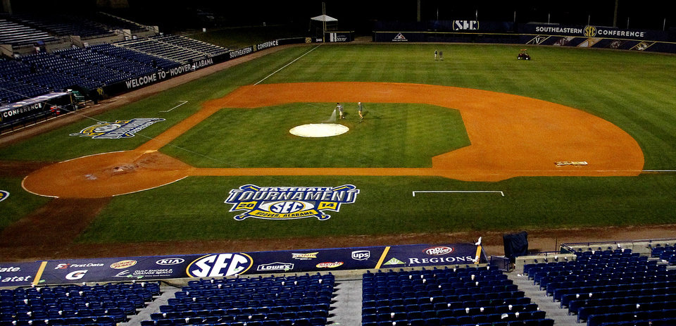 Photo - In this May 24, 2014 photo, ground crew members spray the field after a game at the Southeastern Conference NCAA college baseball tournament in Hoover, Ala. (AP Photo/Butch Dill)