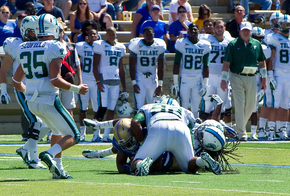 Photo -   In this photo provided by the University of Tulsa, Tulane's Devon Walker, bottom right, and Julius Warmsley (92) tackle Tulsa's Kenny Welcome, bottom left, during the first half of an NCAA college football game in Tulsa, Okla., Saturday, Sept. 8, 2012. On this play, Walker was seriously hurt. (AP Photo/University of Tulsa, John Lew)