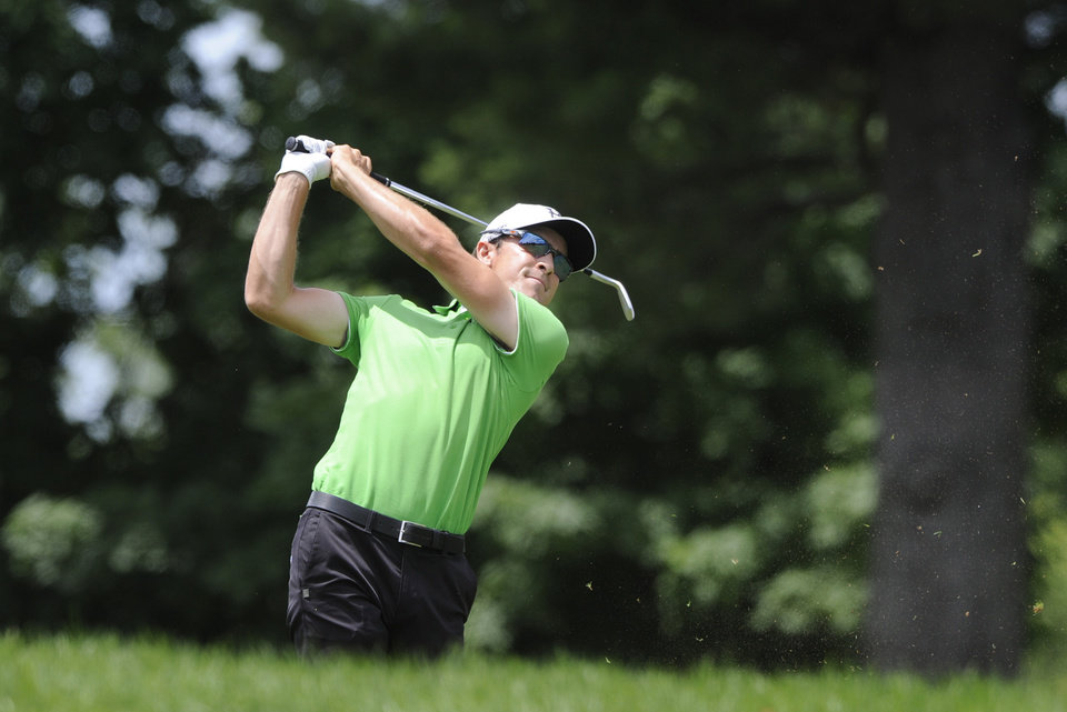 Photo - Scott Langley watches his approach shot on the ninth hole during the second round of the Travelers Championship golf tournament in Cromwell, Conn., Friday, June 20, 2014. (AP Photo/Fred Beckham)