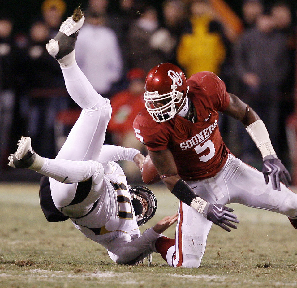 Photo - Oklahoma's Nic Harris (5) forces a fumble on Missouri's Chase Daniel (10) during the first half of the Big 12 Championship college football game between the University of Oklahoma Sooners (OU) and the University of Missouri Tigers (MU) on Saturday, Dec. 6, 2008, at Arrowhead Stadium in Kansas City, Mo. 