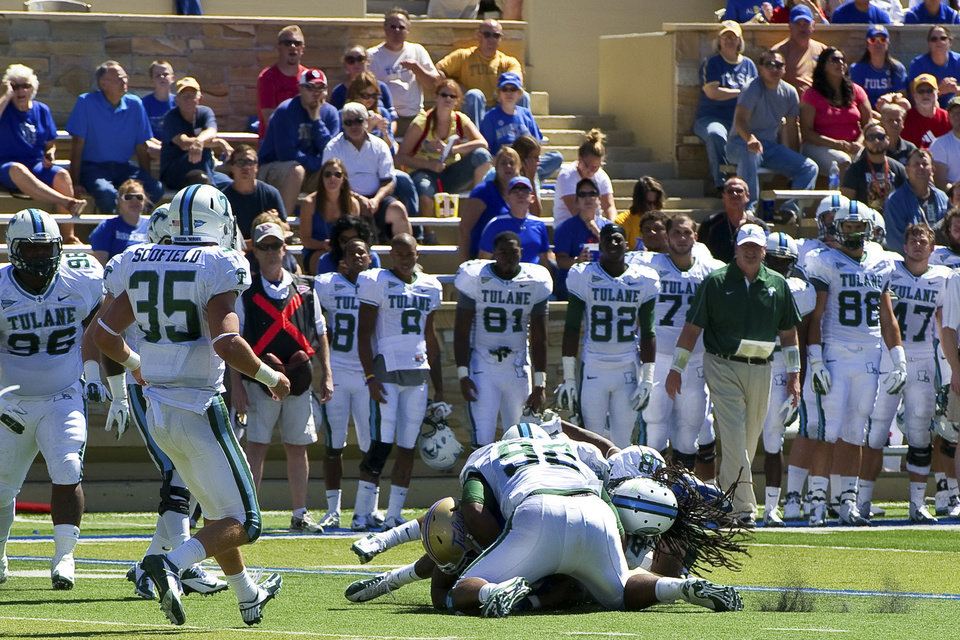 Photo -   In this photo provided by the University of Tulsa, Tulane's Devon Walker (18) and Julius Warmsley (92) tackle Tulsa's Kenny Welcome during the first half of an NCAA college football game in Tulsa, Okla., Saturday, Sept. 8, 2012. On this play, Walker was seriously hurt. (AP Photo/University of Tulsa, John Lew)