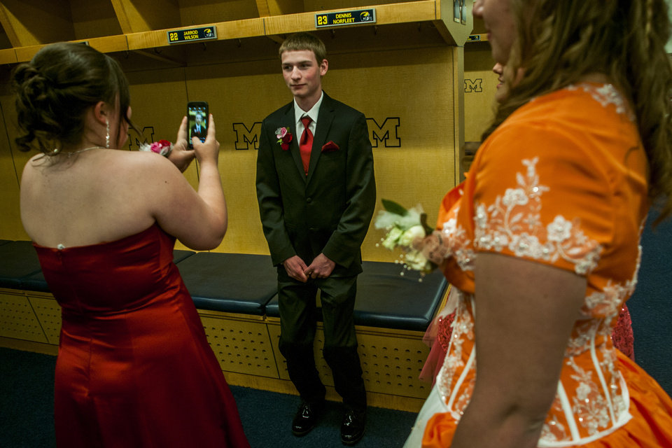 Photo - Students take pictures in the Michigan football locker room at Michigan Stadium on the University of Michigan campus, Saturday, May 10, 2014, in Ann Arbor, Mich. The junior-senior prom for students at Durand High School was the first prom hosted by the 100,000-plus-seat football venue. The group took photos on the field, visited the locker rooms and had their dancing and dinner in the Jack Roth Stadium Club until midnight. (AP Photo/The Flint Journal, Jake May) LOCAL TV OUT; LOCAL INTERNET OUT