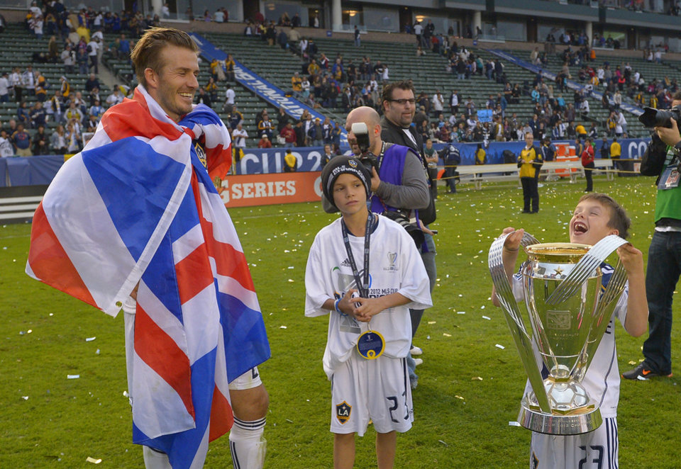 Los Angeles Galaxy midfielder David Beckham, left, looks on along with his son Romeo, center, as his other son Cruz lifts the MLS Trophy after the Galaxy won the MLS Cup championship soccer match 3-1 against the Houston Dynamo, Saturday, Dec. 1, 2012, in Carson, Calif.  (AP Photo/Mark J. Terrill)