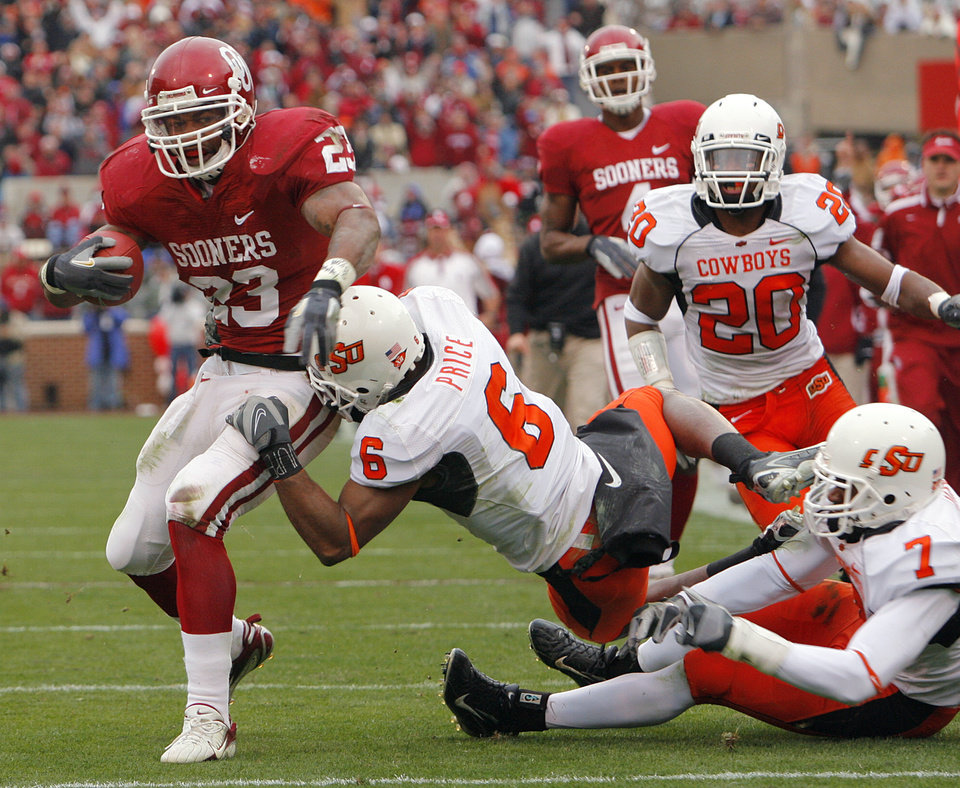 Photo - Oklahoma's Allen Patrick (23) gets past Oklahoma State's Ricky Price (6) during the first half of the college football game between the University of Oklahoma Sooners (OU) and the Oklahoma State University Cowboys (OSU) at the Gaylord Family-Memorial Stadium on Saturday, Nov. 24, 2007, in Norman, Okla. 