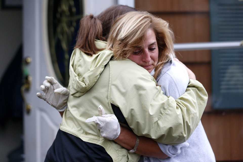 Photo - Kathleen Seemar, right, gets a hug from friend Ginny Baker while taking a break from cleaning out her flooded home to talk to friends as residents of Brick, N.J., cope following superstorm Sandy, Thursday, Nov. 1, 2012. Three days after Sandy slammed the mid-Atlantic and the Northeast, New York and New Jersey struggled to get back on their feet, the U.S. death toll climbed to more than 80, and more than 4.6 million homes and businesses were still without power. (AP Photo/Julio Cortez) ORG XMIT: NJJC112