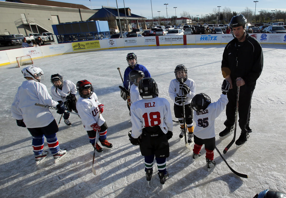The referee talks with players at the Oklahoma City Youth Hockey Association's 8 and under league play at the Norman Outdoor Holiday Ice Rink on Saturday, Dec. 22, 2012 in Norman, Okla. Photo by Steve Sisney, The Oklahoman