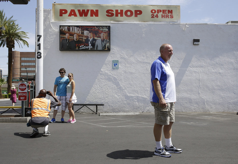 Photo - Randy Renfro, right, and others have their picture taken at the Gold & Silver Pawn Shop in Las Vegas Monday, July 28, 2014, in Las Vegas. Rick Harrison, owner of the pawn shop and one of the stars of the reality television series Pawn Stars, has proposed building a shopping plaza on land nearby. (AP Photo/John Locher)