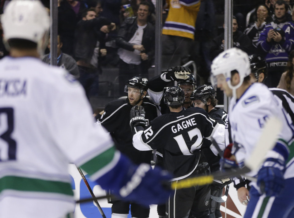 Members of the Los Angeles Kings celebrate Anze Kopitar's goal as Vancouver Canucks defenseman Kevin Bieksa, left, and Maxim Lapierre looks on  during the second period of an NHL Hockey game in Los Angeles, Monday, Jan. 28, 2013. (AP Photo/Chris Carlson)