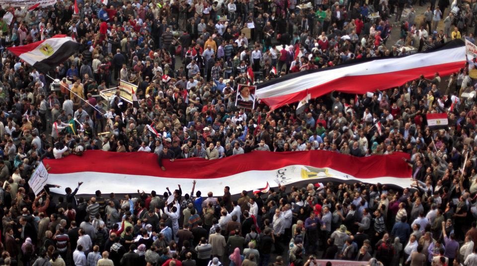 Egyptian protesters carry large national flags in Tahrir Square in Cairo, Egypt, Tuesday, Nov. 27, 2012. Thousands flocked to Cairo\'s central Tahrir square on Tuesday for a protest against Egypt\'s president in a significant test of whether the opposition can rally the street behind it in a confrontation aimed at forcing the Islamist leader to rescind decrees that granted him near absolute powers. (AP Photo/ Khalil Hamra)