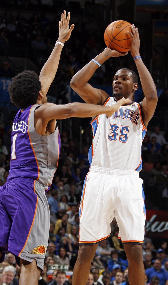 Photo - Oklahoma City's Kevin Durant (35) shoots over Josh Childress (1) of Phoenix in the third quarter during the NBA basketball game between the Oklahoma City Thunder and Phoenix Suns at Chesapeake Energy Arena in Oklahoma City, Saturday, Dec. 31, 2011. Oklahoma City won, 107-97. Photo by Nate Billings, The Oklahoman