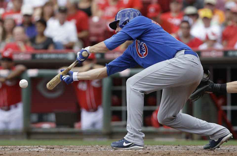 Photo - Chicago Cubs' Kyle Hendricks lays down a sacrifice bunt in the fifth inning of a baseball game against the Cincinnati Reds, Thursday, July 10, 2014, in Cincinnati. Hendricks was making his major league debut. (AP Photo/Al Behrman)