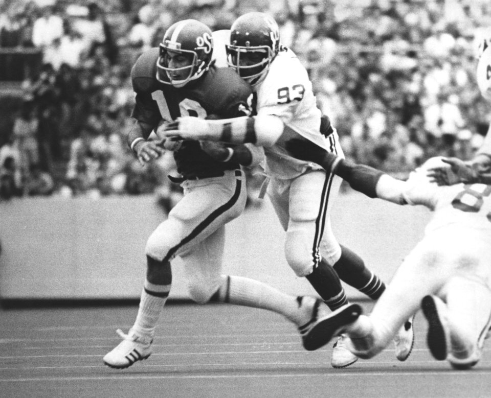 OU defensive lineman Lee Roy Selmon wraps up Oklahoma State University quarterback Scott Burk during a Bedlam college football game as the Sooners went on to defeat the Cowboys in Stillwater by a 27-7 score on Nov. 1, 1975. Staff photo by J. Pat Carter taken