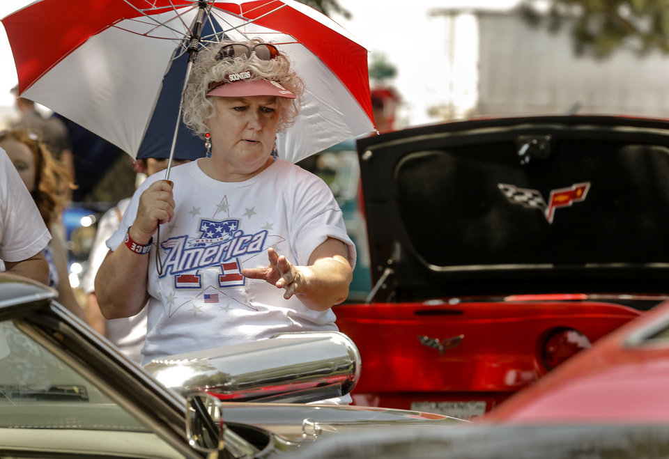 Dorinda Mayhue looks at cars on display in the car show during the Yukon Freedom Fest at the Yukon City Park on Thursday , July 4, 2013, in Yukon, Okla. Photo by Chris Landsberger, The Oklahoman