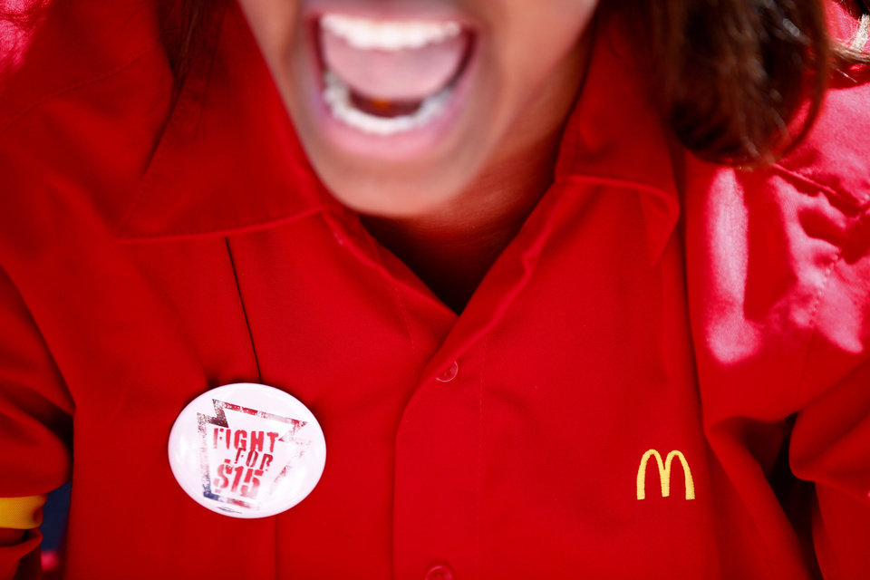 Photo - A fast-food worker is chants slogans before being detained by police during a protest to push fast-food chains to pay their employees at least $15 an hour, outside a McDonald's restaurant Thursday, Sept. 4, 2014, in Philadelphia. The protest movement, which is backed financially by the Service Employees International Union and others, has gained national attention at a time when the wage gap between the poor and the rich has become a hot political issue.   (AP Photo/Matt Rourke)