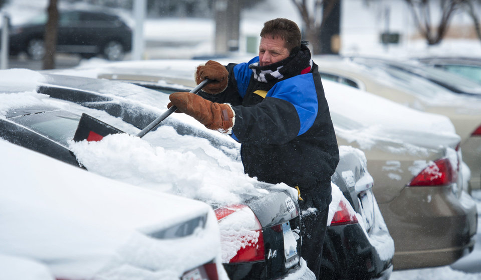 Photo - Gene Fritz clears snow from new vehicles at Valley Buick, Thursday morning, Dec. 20, 2012 in Apple Valley, Minn. The first widespread snowstorm of the season crawled across the Midwest on Thursday, with whiteout conditions stranding holiday travelers and sending drivers sliding over slick roads _ including into a fatal 25-vehicle pileup in Iowa. (AP Photo/The Star Tribune, Glen Stubbe)  MANDATORY CREDIT; ST. PAUL PIONEER PRESS OUT; MAGS OUT; TWIN CITIES TV OUT