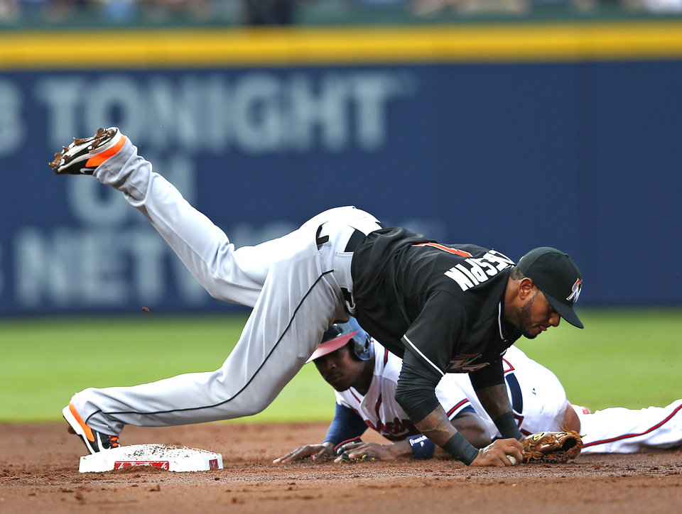 Photo - Atlanta Braves' Justin Upton is forced out at second base by Miami Marlins second baseman Jordany Valdespin (1) on a Jason Heyward ground ball in the second inning of a baseball game  Thursday, July 24, 2014. in Atlanta (AP Photo)