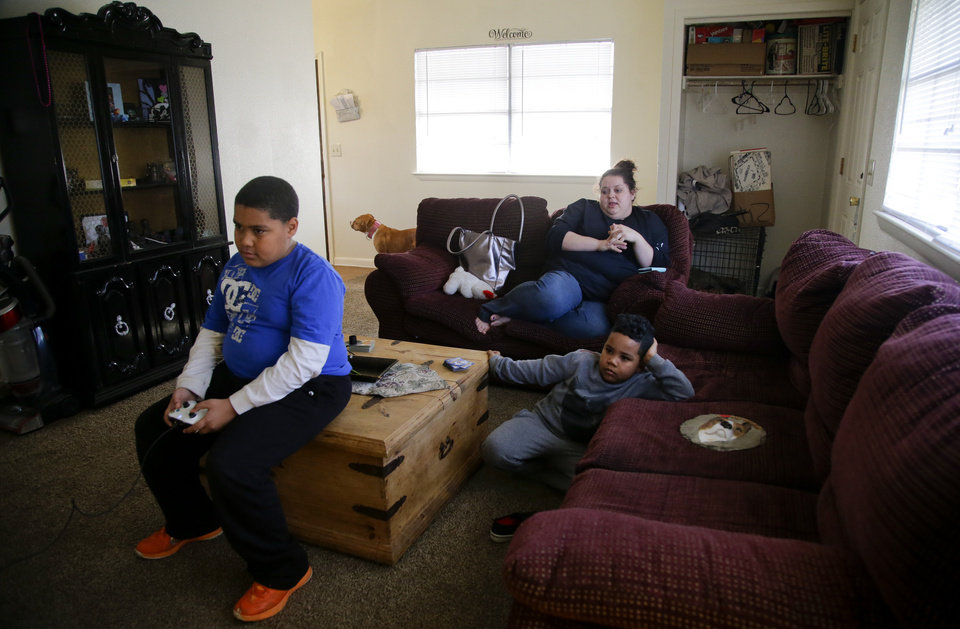 Photo -  Desha Bailey watches her son, Jakobie Roberson, left, 10, play the video game