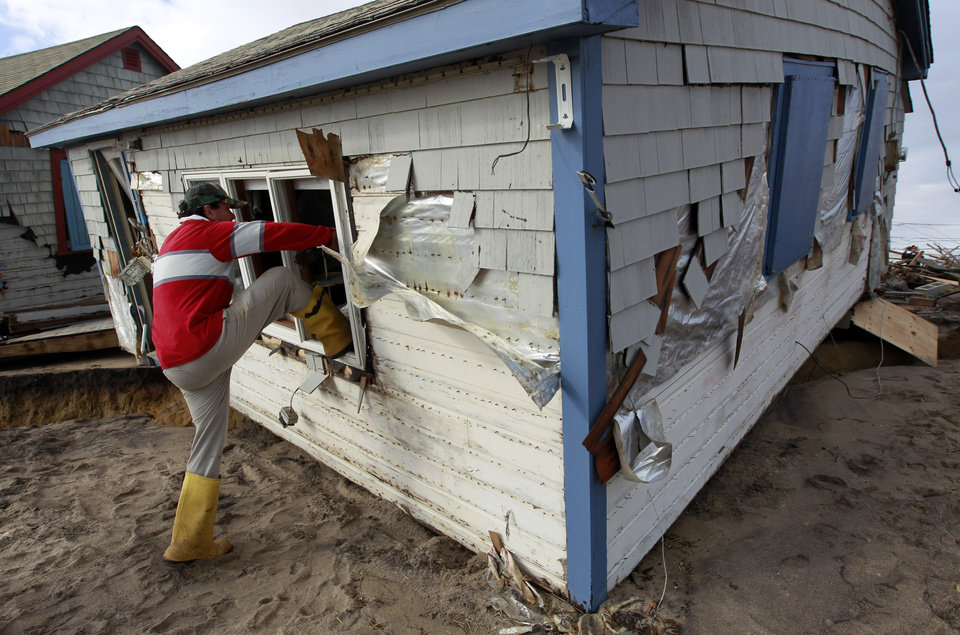 Christopher Hannafin, of South Kingstown, R.I., enters a friend's cottage through a window to salvage belongings from the structure destroyed by Superstorm Sandy, on Roy Carpenter's Beach, in the village of Matunuck, in South Kingstown, Tuesday, Oct. 30, 2012. Sandy, the storm that made landfall Monday, caused multiple fatalities, halted mass transit and cut power to more than 6 million homes and businesses. (AP Photo/Steven Senne) ORG XMIT: RISR105