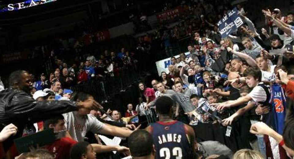 Photo - Fans cheer for Cleveland's  LeBron  James as he leaves the court following the NBA game between the Oklahoma City Thunder and the Cleveland Cavaliers, Sunday, Dec. 13, 2009, at the Ford Center in Oklahoma City. Photo by Sarah Phipps
