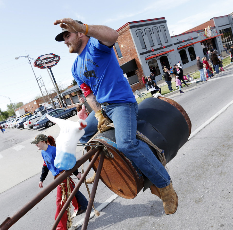 Photo - Derek May rides a barrell bull ride attached to the power lift on a tractor in the 89er Day Parade on Saturday, April 20, 2013 in Norman, Okla.  Photo by Steve Sisney, The Oklahoman
