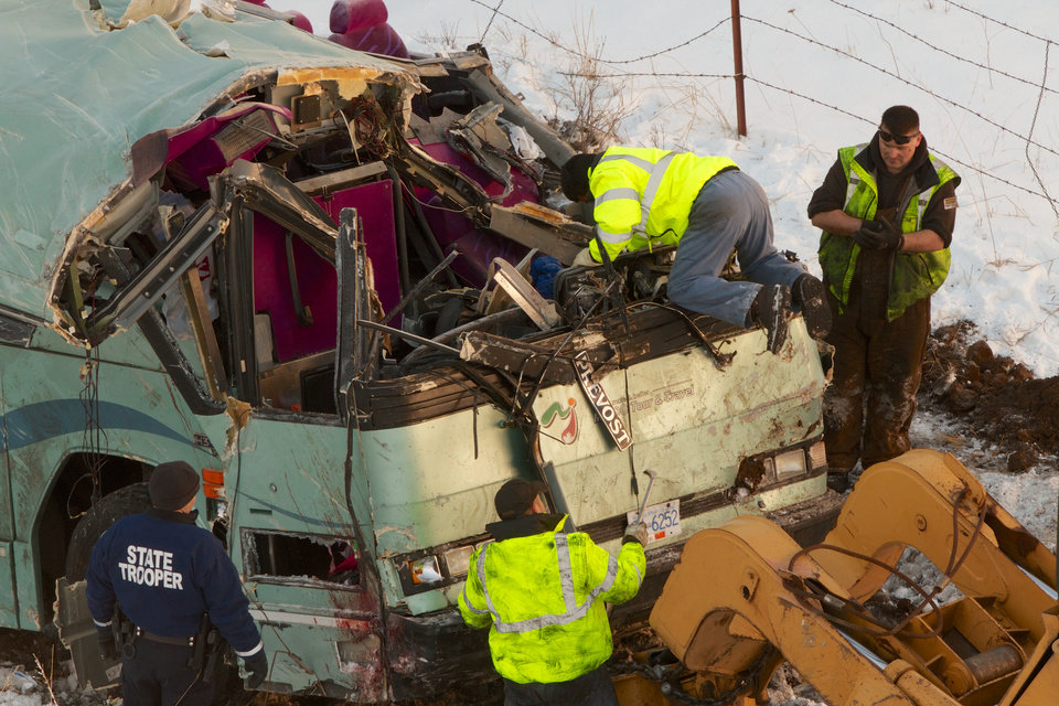 Photo - Workmen move the bus which plummeted 200 feet down an embankment in rural Eastern Oregon Sunday, killing nine and sending multiple to hospitals, Monday, Dec. 31, 2012. Survivors of the bus crash said Monday some passengers were thrown from the tour bus through broken windows after the vehicle skidded out of control, smashed through a guardrail and went down. (AP Photo/The Oregonian, Randy L. Rasmussen)