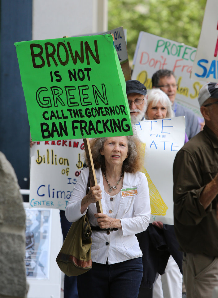 Photo - About a dozen environmentalists protest outside the auditorium where Gov. Jerry Brown spoke about climate change at the University of California  Giannini Foundation of Agricultural Economics conference in  Sacramento, Calif., Monday, May 19, 2014.(AP Photo/Rich Pedroncelli)