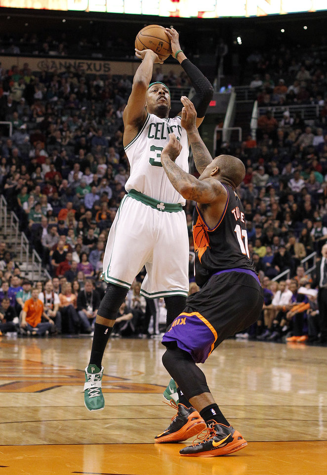Boston Celtics forward Paul Pierce, left, attempts to score over Phoenix Suns forward P.J. Tucker, right, in the first half of an NBA basketball game, Friday, Feb. 22, 2013, in Phoenix. (AP Photo/Paul Connors)