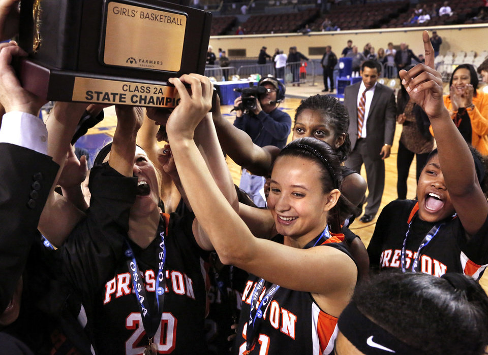 Photo - Preston players Alison Raley, #20, and Tristin Flora, #21, join teammates in holding the state championship trophy at the end of the Class 2A Girls State Championship game between Preston and Cordell at Jim Norick Arena at State Fair Park  on Saturday, Mar. 15, 2014.  Preston won,  45-41. Photo by Jim Beckel, The Oklahoman
