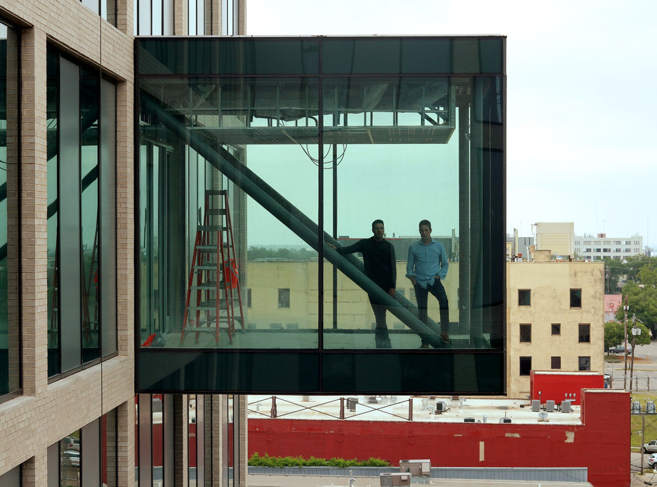 Photo - David, left, and Andy Burnett in the 6th floor conference room that extends outside of the building. Heartland building progress in downtown at 5th and Broadway, Wednesday, May 13, 2020. [Doug Hoke/The Oklahoman]